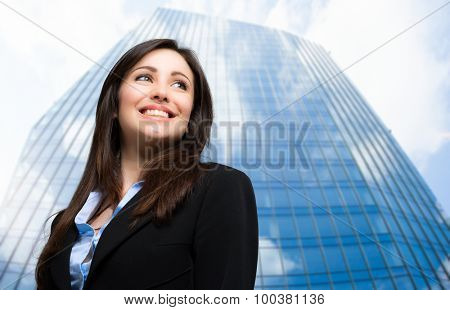 Portrait of a smiling business woman in front of a skyscraper