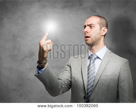 Portrait of a businessman looking surprised at his lighten-up finger