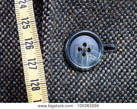 Measuring Tape And Buttoned Button On Tweed Jacket