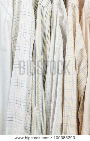 Various Male Shirts On Hangers In Wardrobe