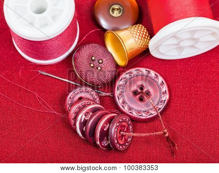 Sewing Thread, Buttons, Thimble On Red Textile
