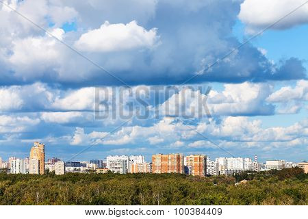 Low Blue Clouds Over Green Forest And City