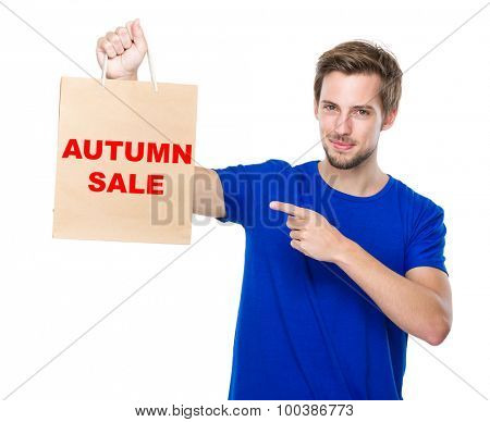 Man finger point to the shopping bag and showing phrase autumn sale