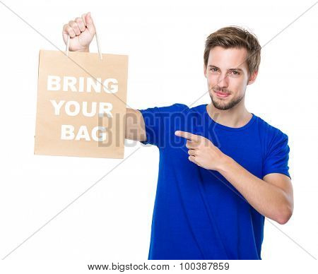 Man finger point to the shopping bag and showing phrase bring your bag