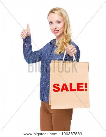 Woman with shopping bag and thumb up for showing a word sale!