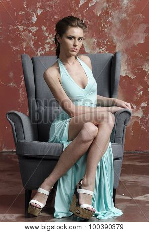 Young beautiful brown-haired woman in blue light silk dress with open shoulders and a long skirt
