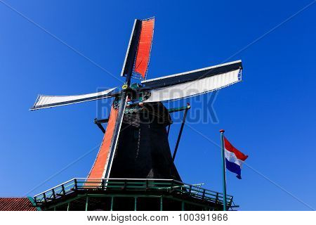 Classic Dutch windmill with The Dutch national flag