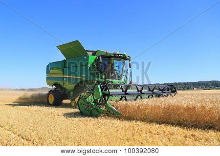 John Deere Combine S670I Harvests Barley On A Sunny Day