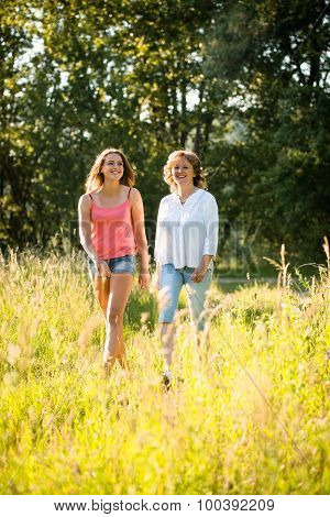 Mother and teenage daughter walk in nature