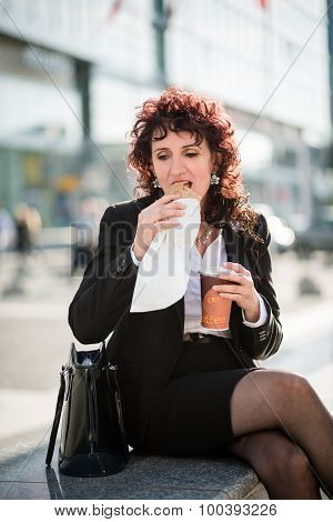 Quick lunch - business woman eating in street