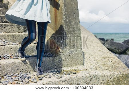 Legs Of Woman In Dress Standing On Coast