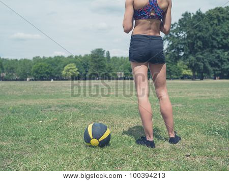 Woman Standing In Park With Medicine Ball
