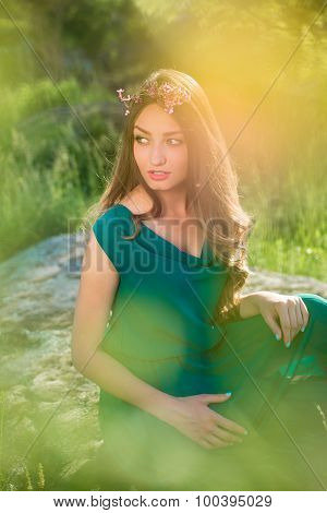 Pretty lady wearing green dress and flowers in long hair