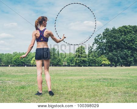 Woman Twirling Hula Hoop In Park
