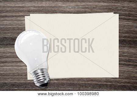 Incandescent light bulb and and paper on wood background