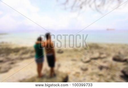 Man And Woman Standing Arm In Arm On A Rock By The Sea,blurred For Presentation Effect, Abstract Bac