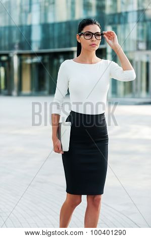 Confident young businesswoman adjusting her eyeglasses