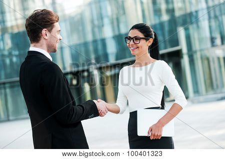 Smiling young business people shaking hands