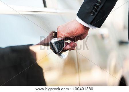 Closeup of businessman's hand on car door