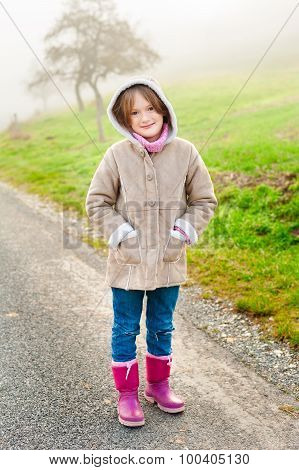 Outdoor portrait of a cute little girl on a foggy day, wearing warm beige coat and pink boots