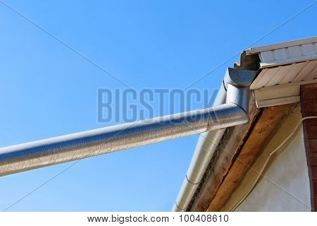 The gutter on the roof on blue sky background