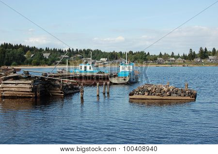 Two fishing motor boats are docked on a lake.