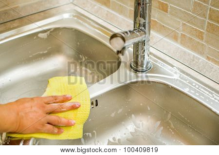 Woman Hand Doing Chores In The Kitchen At Home , Sink And Faucet With Yellow Sponge