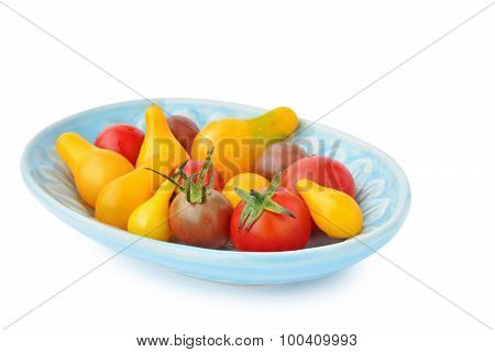 Assortment Of Heirloom Cherry Tomatoes In Blue Bowl Isolated