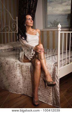 Attractive Brunette Sitting On The Bed