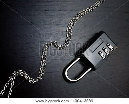 small black combination lock thin stell chain metal black background elegant