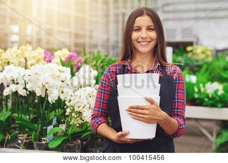 Happy Young Florist Working In A Hothouse