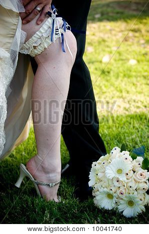 Groom's hand on bride's leg with blue and white garter exposed