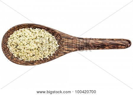 hemp seeds hearts on a wooden spoon isolated on white