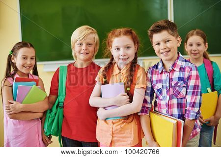 Happy schoolkids with books looking at camera