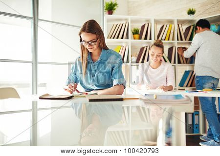 Pretty teenage girl reading sms on background of her groupmates before lesson