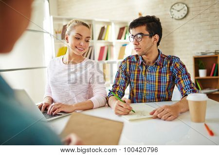 Group of teenage girl with laptop and guy with pencil and notepad doing home task together