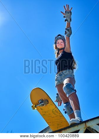 Portrait of teen girl hand up standing on his skateboard aganist blue sky outdoor.