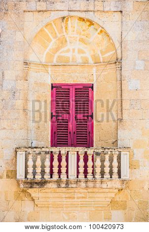 arched balcony with traditional Maltese colorful door in Mdina