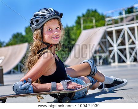 Teen girl in helmet sitting on his skateboard outdoor.