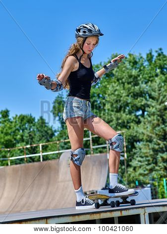 Teen girl rides his skateboard outdoor. Girl do  stunt aganist blue sky.
