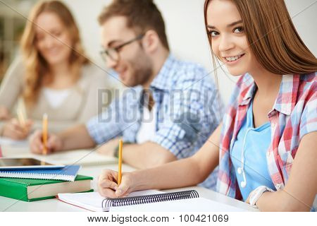 Smiling girl carrying out written task with her groupmates on background