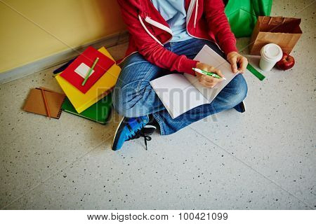 Schoolboy making notes in exercise-book while sitting on the floor