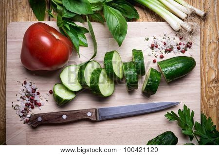 Cooking of salad with fresh vegetables, tomatoes, cucumbers and herbs