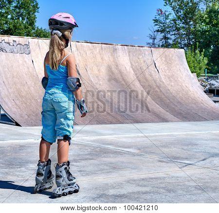 Girl riding on roller skates in skatepark. View from the back