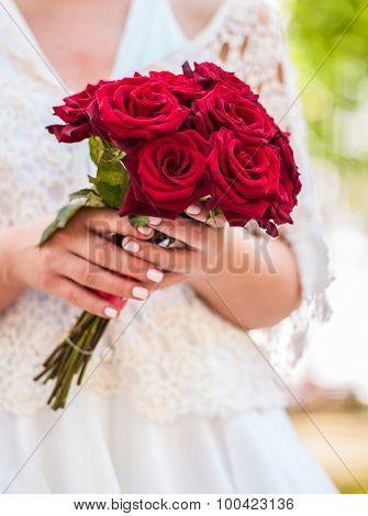 Bride holding red rose flower at summer outdoor.
