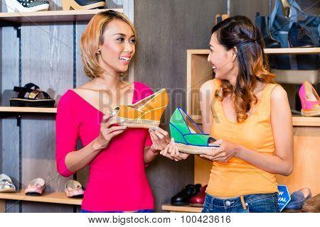 Asian girl friends shoe shopping in store