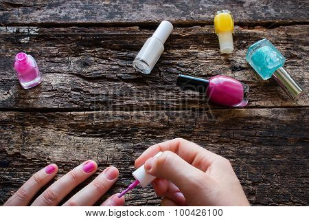 Young Woman Paints Her Nails Pink Polish