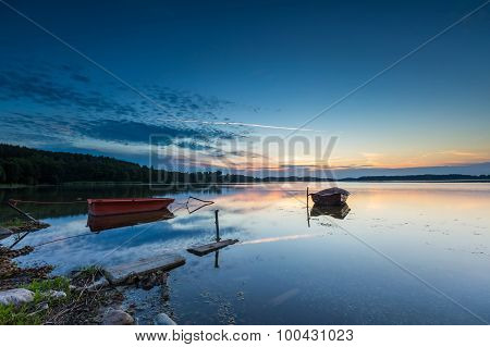 Fisherman Boats Moored On Lake Shore Under Sunset Sky