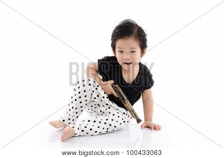 Cute Asian Boy Sitting  And Holding Toy Antique Gun On White Background