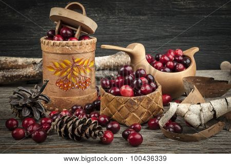 Fresh ripe cranberries in birch bark and wooden traditional containers on rustic dark wood background